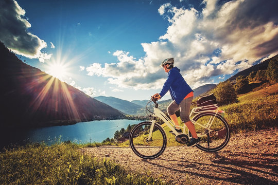 woman on e-bike enjoying view to a beautiful lake
