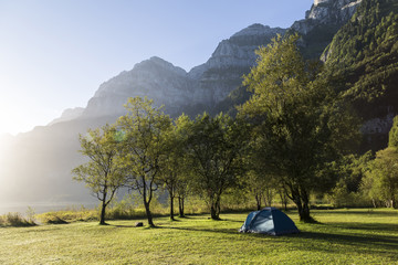 Tourist tent  in  mountains. Camping holidays. Alps. Switzerland.