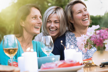 three female friends in their 40s share a moment of complicity. They gathered around a table in the garden to share a meal with friends.