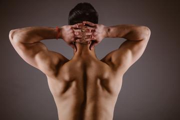 Man muscular back on dark background