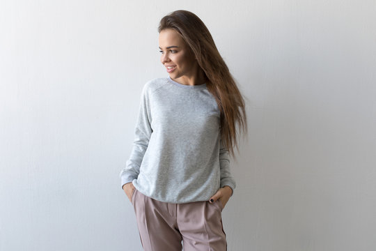 Beautiful woman in gray sweatshirt stands on white background. Mock-up.