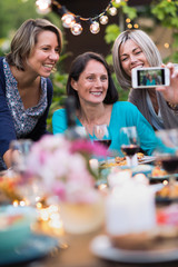 Summertime. Group of friends gathered around a table in the garden to share a meal. Three beautiful women in their forties taking a selfie
