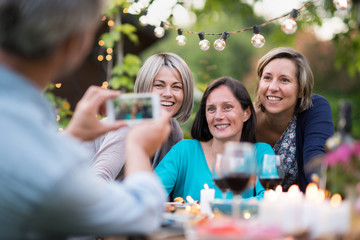 One summer evening friends gathered around a table in the garden for a good time. A man takes a picture of three female friends in their forties
