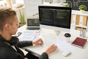 Portrait of contemporary young man coding at modern computer sitting at desk and working in startup project, focus on computer screen, copy space