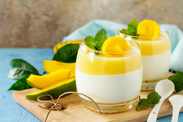 Papiers peints Dessert Mango panna cotta with fresh mango and topping with mango jelly on a stone or slate background. Traditional italian dessert. Copy space.