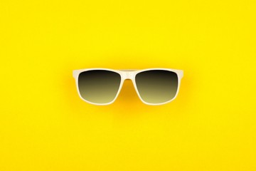 Sunglasses with bright yellow background. Top view, minimal summer concept.