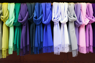 Colorful hanging display of wool scarves