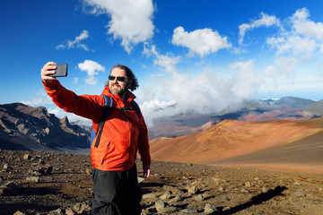 Tourist taking a photo of himself in Haleakala volcano crater on the Sliding Sands trail. Maui, Hawaii, USA.