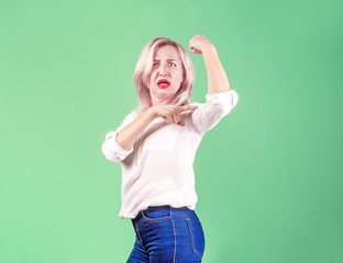 crazy strong confident a woman looks at her biceps and expresses extreme discontent and anger. Impotence concept