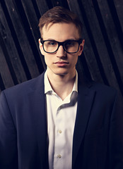 Serious successful business man looking in suit and trendy eyeglasses on black studio dark background. Front toned closeup portrait