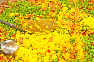 top view, close up of freshly prepared paell,  red peppers, spanish sasuage, chicken bits, stock, large heated pan with red handles at a spanish wine tasting event in a tropical resturant
