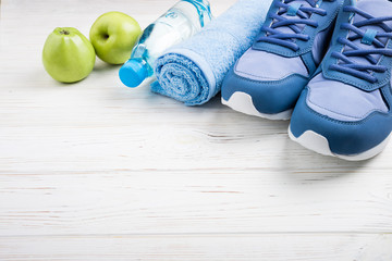 Flat lay sport shoes, bottle of water, apples, towel and earphones on white wooden background. Sport equipment. Healthy lifestyle, sport and diet concept. Copy space