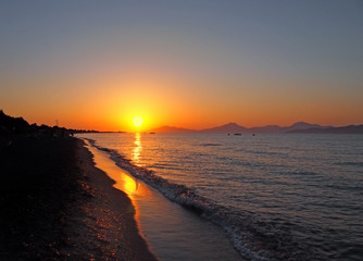 beautiful golden sunset reflected on the sea and wet beach sand in Kos Greece