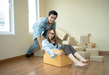 Happy couple having fun young man pushing  young woman sitting on cardboard box looking at camera,cheerful roommates playing while packing unpacking belongings together
