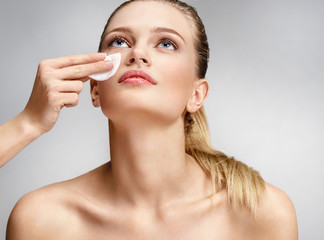 Makeup artist making the face cleaning with a cotton pad. Photo of beautiful woman with natural makeup on grey background. Skin care and beauty concept.