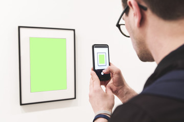 Young handsome man taking a photo of abstract image in art museum. Concept of creative mock up screen.