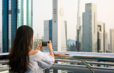 Girl taking picture of Dubai cityscape