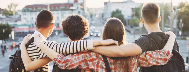 Friendship, traveling, sightseeing, adventure, togetherness, student exchange program. Young people with backpacks standing close hugging at city background - fototapety na wymiar
