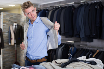 Portrait of buyer man choosing waistcoat