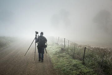 Photographer walks through morning fog