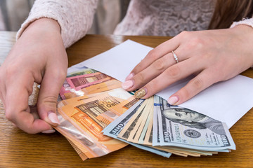 Envelope full of euro and dollar with female hands