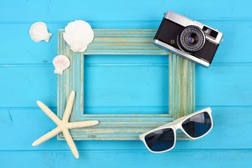 Beach travel concept mock up with frame, shells, sunglasses and camera on blue wood background. Flay lay with copy space.
