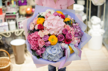 Girl holding a beautiful bright bouquet of pink, blue and crimson flowers