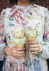 Woman's hands is holding two ice cream on a background of bright summer dress Summer. Vacation.