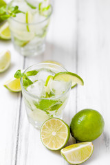 Summer refreshing cocktail mojito with lime and mint on white wooden vintage background.