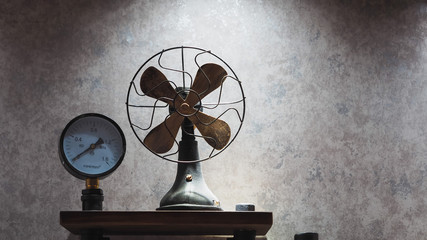 Closeup Shot of Vintage Electric Fan and A Pressure Gauge (mpa / mm2) on Concrete Polishing Wall Background in Dingy Light for Interior Works or Decoration.
