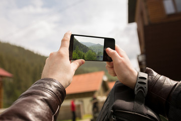 Male tourist taking picture in the mountains of the Carpathians on his smartphone