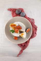 tasty camembert with fresh figs and honey with honeycombs, decorated on a white wood plate background, rustic, moody food photography