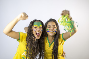 Girls fans of the Brazil team with their faces painted celebrating the result of the game - Celebrating a goal