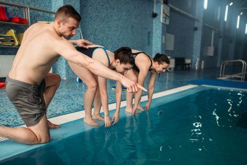 Instructor and female swimmers in swimming pool