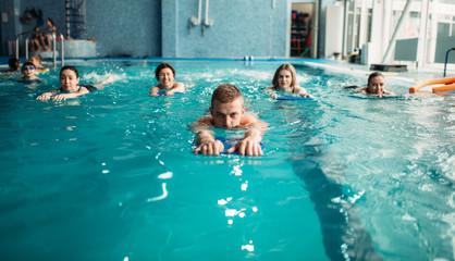 Male trainer swims with female aqua aerobics group