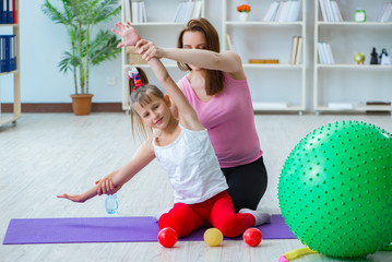 Girl and mother exercising at home