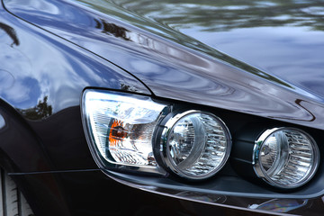 The headlight on a brown car, close-up, polished glass for road lighting while driving.