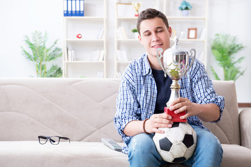 Young man student watching football at home