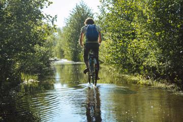 Junger Mann fährt durch überschwemmten Weg