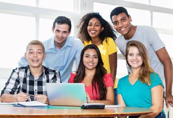 Lehrer und Schüler schauen zur Kamera