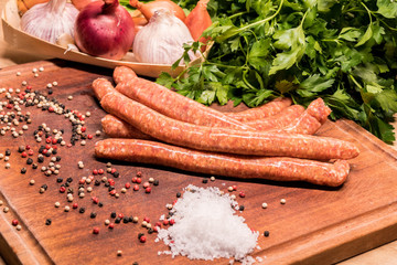 raw sausages with chilli and herbs on a wooden board with spices