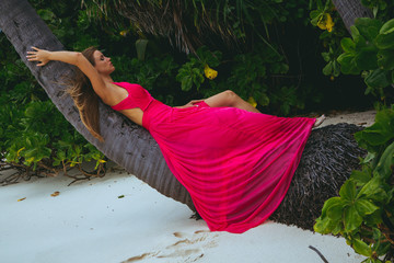 Beautiful girl lying on a palm at the beach on Maldives.