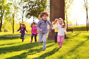 many young children smiling running along the grass in the park. Childhood, Children's Day, vacation, vacation, adventure, friendship.