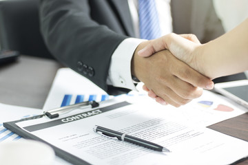 Two businessmen shaking hand after successful negotiate and signing on contract about working and partner together.