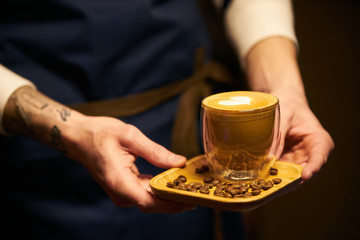 Barista in dark apron uniform holding a cup of coffee with latte art