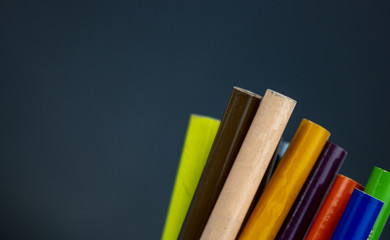 The ends of colored pencils stick out on a dark chalkboard background. Back to school colored pencils with lots of room for text!