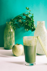 Healthy green smoothie with kale banana and date in glass against a green background. Detox, diet, healthy, vegetarian food concept with copy space.+