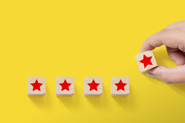Hand putting wood block with five star symbol to increase rating of company with yellow background, Copy space for text or headline