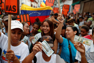 "Supporters of Venezuelan presidential candidate Henri Falcon, holding fake hundred dollar bills that read, ""Dollarization with Henri Falcon"", attend to a campaign rally in Caracas"