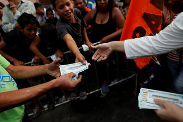 "Supporters of Venezuelan presidential candidate Henri Falcon hold fake hundred dollar bills that read, ""Dollarization with Henri Falcon"", during a campaign rally in Caracas"